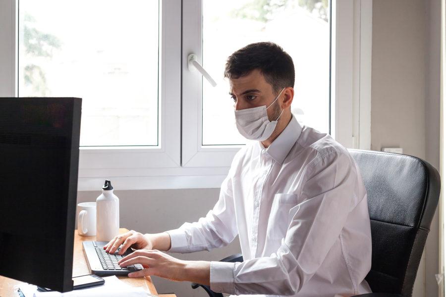 Chico con mascarilla trabajando en el ordenador