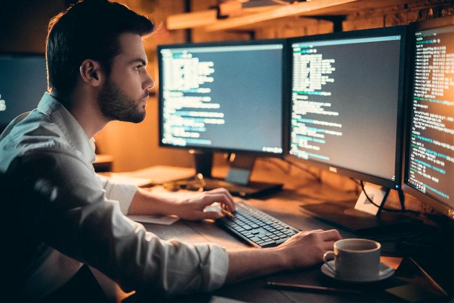 Persona delante de ordenadores viendo código.