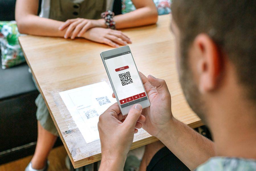 Un hombre escanea un código QR en un restaurante.
